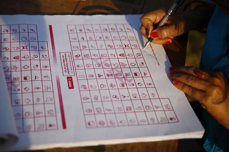 A volunteer signs a mock ballot paper during mock elections. Photo: Skanda Gautam/THT