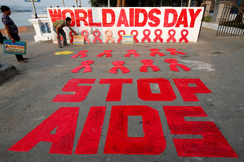 A man places a placard as he prepares a message during an HIV/AIDS awareness campaign on the eve of World AIDS Day in Kolkata, India, November 30, 2017. Photo: Reuters