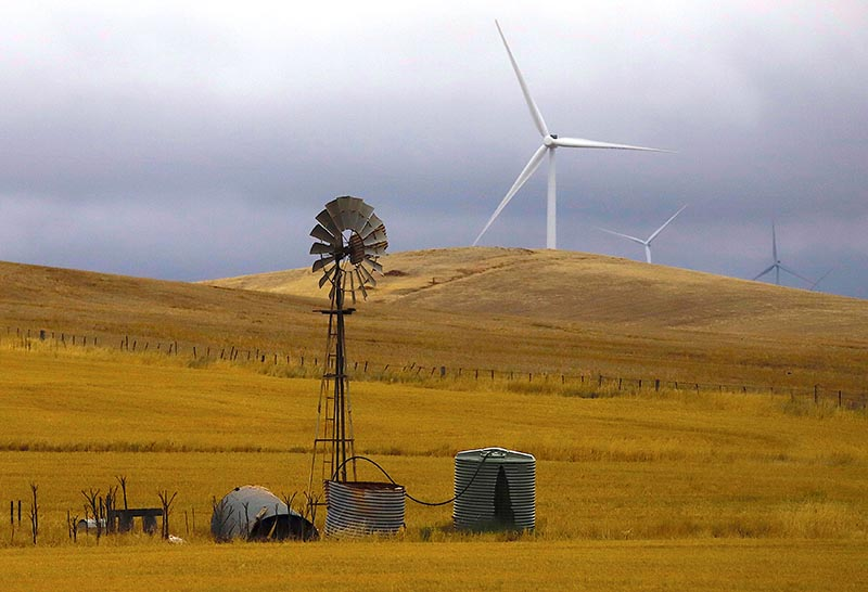 An old windmill stands in front of wind turbines in a paddock near the Hornsdale Power Reserve, featuring the world's largest lithium ion battery made by Tesla, located on the outskirts of the South Australian town of Jamestown, in Australia, on December 1, 2017. Photo: Reuters