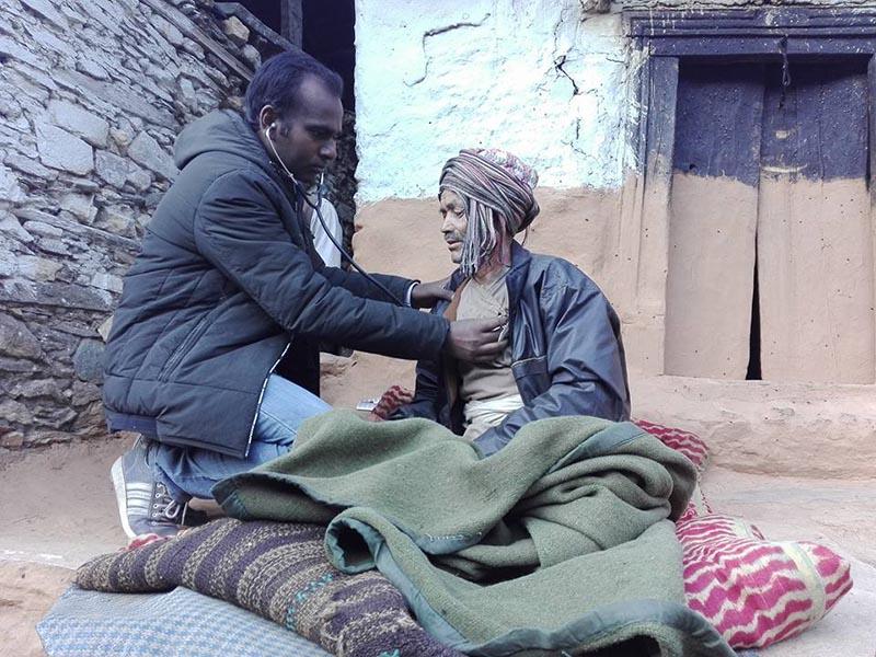 FILE - Dr Bijay Kumar Sah of District Health Office, Bajura, checks a viral fever patient in Swamikartik Rural Municipality-5, of Bajura district, on Monday, December 18, 2017. Photo: Prakash Singh