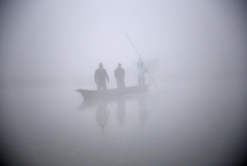 People ride on a boat to reach the bank of Rapti River during the foggy winter morning at Sauraha in Chitwan, Nepal December 26, 2017. Photo: Reuters