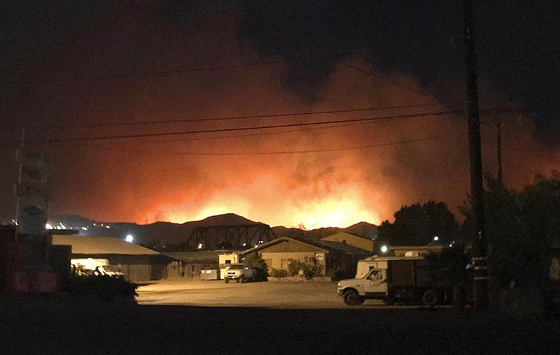 Flames from a wildfire loom up over a neighborhood in Santa Paula, Calfornia, on Monday, December 4, 2017. Photo: Megan Diskin/The Ventura County Star via AP
