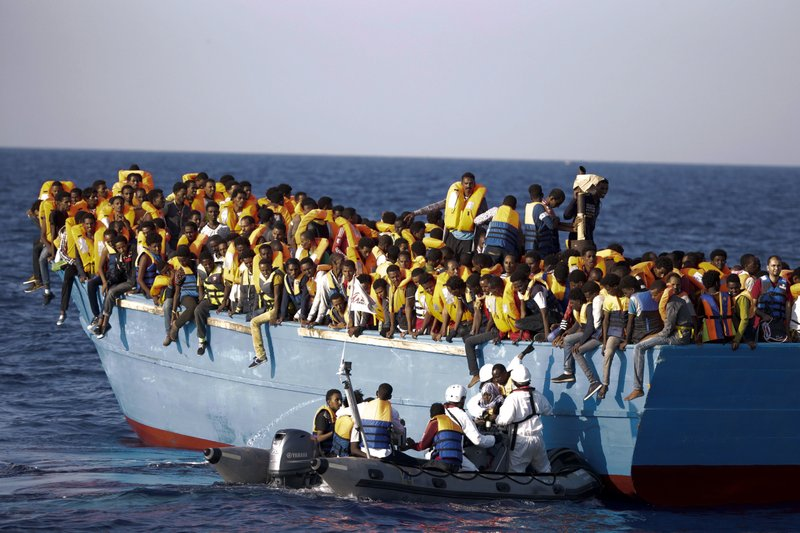 Italian officers rescue a woman from a crowded wooden boat carrying more than seven hundred migrants, during a rescue operation in the Mediterranean sea, about 13 miles north of Sabratha, Libya. Scientists say climate change could dramatically increase the number of people seeking asylum in Europe. Researchers examined asylum applications in the European Union from 2000 to 2014 and found the number was influenced by temperature anomalies in migrantsu2019 home countries, on August 29, 2016. Photo: AP