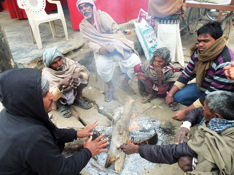 Men gather around woodfire to warm themselves from the cold wave that has affected daily life in Rautahat on Sunday, December 17, 2017. Photo: Prabhat Kumar Jha
