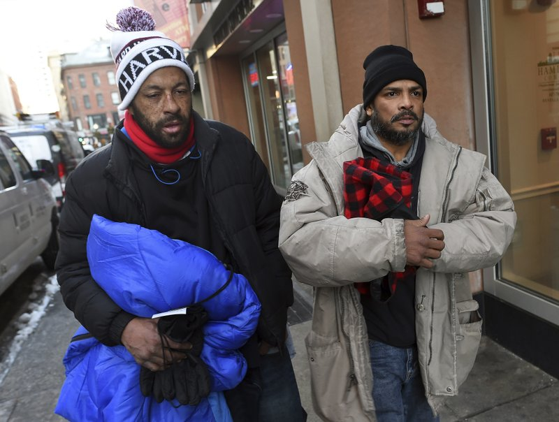 Dec. 27, 2017, photo, homeless men Sean Stuart, left, and Segundo Rivera walk on a street after spending the day at St. Francis House in Boston. With temperatures across Massachusetts not expected to rise above freezing for days, politicians and advocates for the homeless are particularly concerned about getting as many people as possible into shelters. Stuart and Rivera told the Boston Herald that theyu2019re not comfortable spending the night in a shelter. u201cWeu2019ve lived out here so long itu2019s like honestly, this is comfortable for us,u201d Rivera said. (Christopher Evans/The Boston Herald via AP)