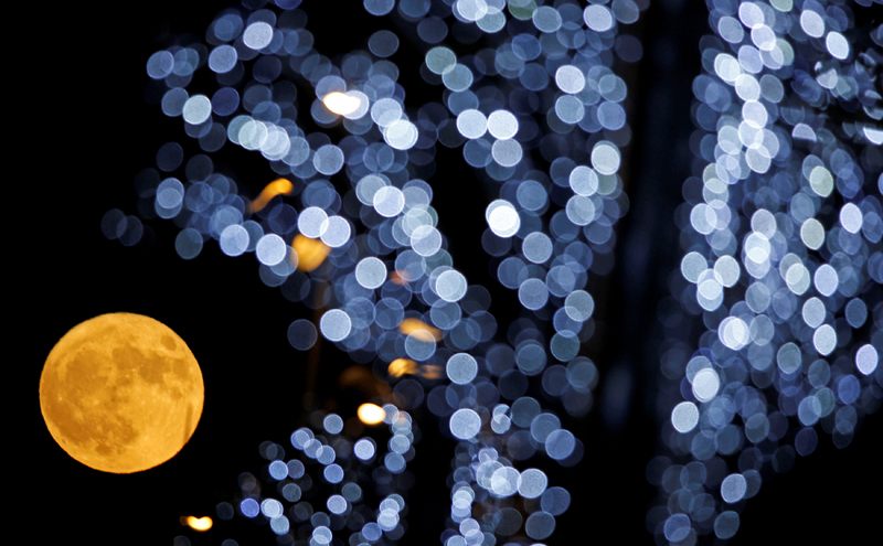The full moon is pictured behind Christmas lights in Marseille, France December 3, 2017. Photo: Reuters