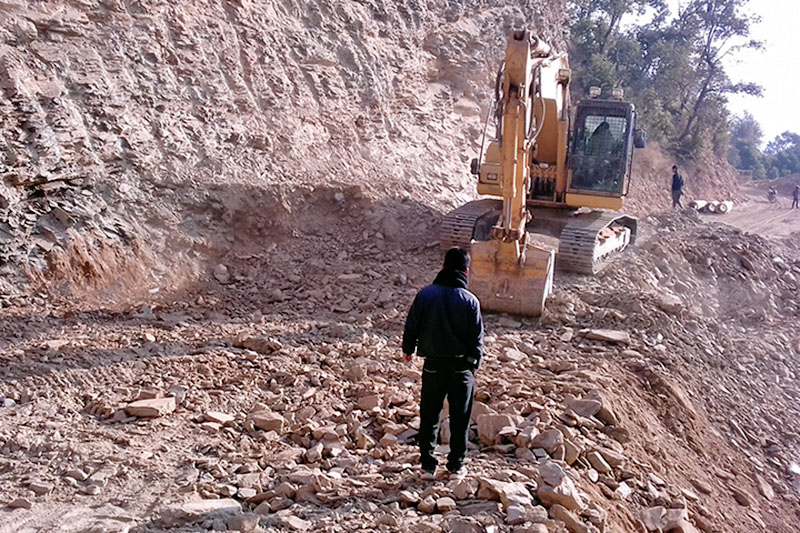 A man looks on as an excavator construct roat along Charepatan-Lameaahal road section in Pokhara Lekhnath Metropolitan City, on Tuesday, December 26, 2017. Photo: RSS