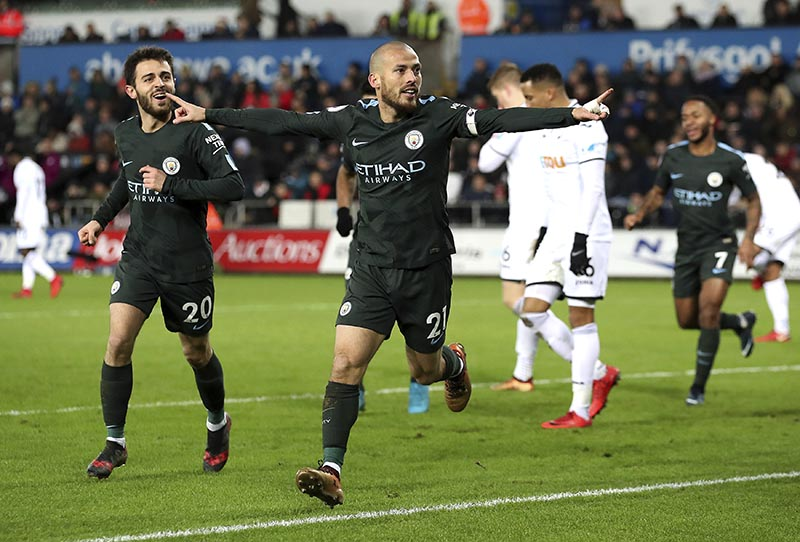 Manchester City's David Silva (centre), scores his side's first goal of the game against Swansea City, during their English Premier League soccer match at the Liberty Stadium in Swansea, England, on Wednesday December 13, 2017. Photo: Nick Potts/PA via AP