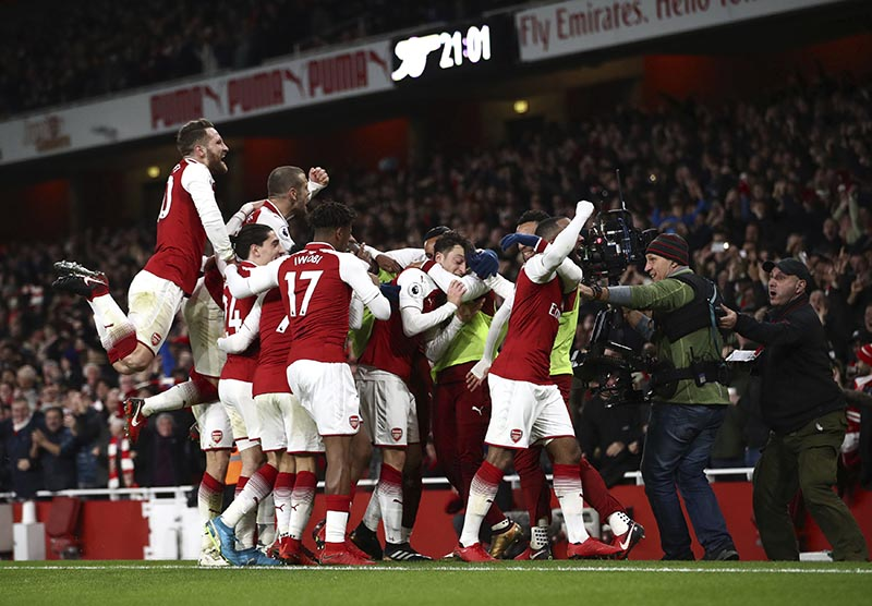 Arsenal's Mesut Ozil (centre) celebrates with teammates after scoring his side's third goal of the game during their English Premier League soccer match between Arsenal and Liverpool at the Emirates stadium London, on Friday, December 22, 2017. Photo: John Walton/PA via AP