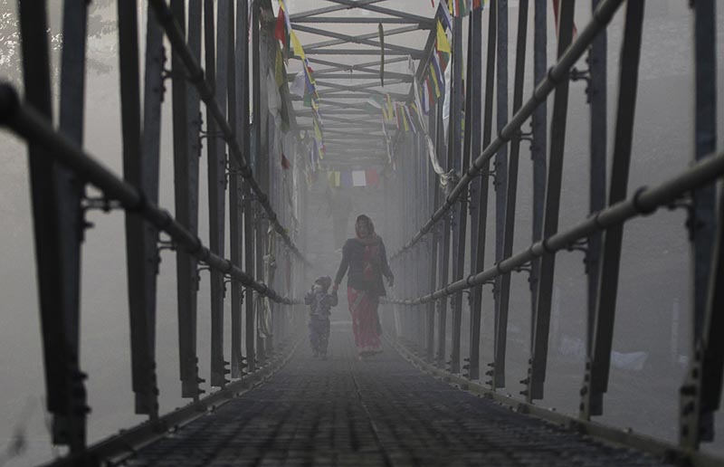A woman with her son walks across a bridge to perform rituals in the fog during Gaya Aunsi festival in Kathmandu, on Monday, December 18, 2017. Photo: AP