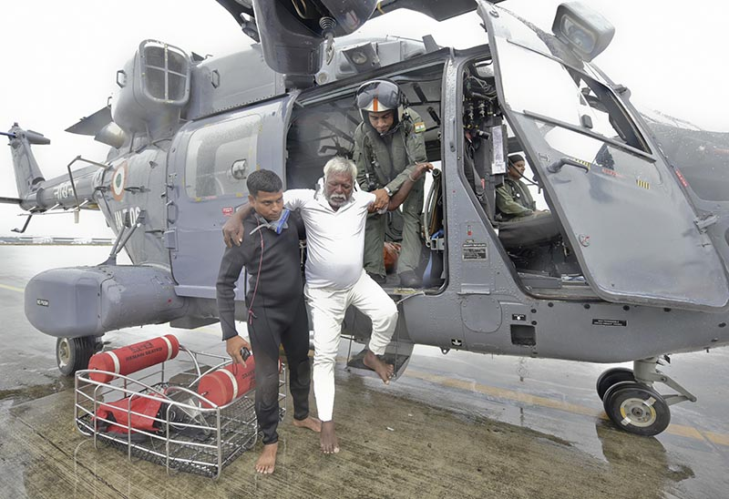 An Indian fisherman who was stranded in the Arabian Sea is escorted down from an Indian Navy helicopter after being rescued in Thiruvananthapuram, Kerala state, India, on Friday, December 1, 2017. Photo: AP