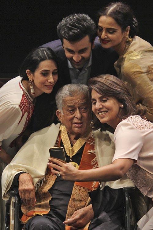 Bollywood actors (clockwise from left), Karisma Kapoor, Ranbir Kapoor, Rekha and Neetu Singh pose for a selfie with Veteran Bollywood actor Shashi Kapoor (sitting), at a ceremony where Shashi Kapoor was conferred the Dadasaheb Phalke Award, in Mumbai, India, on May 10, 2015. Photo: AP/ File
