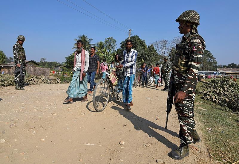 Villagers walk past Central Reserve Police Force (CRPF) personnel patrolling a road ahead of the publication of the first draft of the National Register of Citizens (NRC) in the Juria village of Nagaon district in the northeastern state of Assam, India, on December 28, 2017. Photo: Reuters