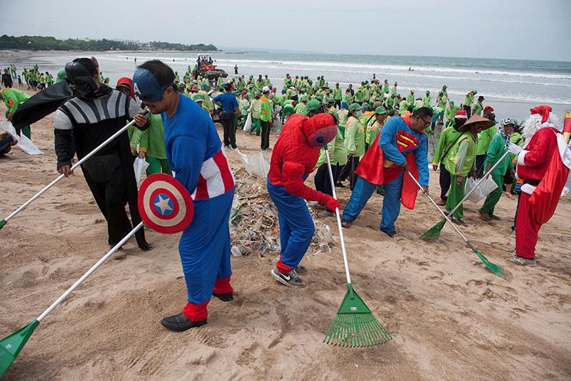 Workers wearing super hero costumes to attract tourist, sweep up garbage at Kuta Beach, Bali, Indonesia, on December 27, 2017. Photo: Antara Foto/Nyoman Budhiana via Reuters