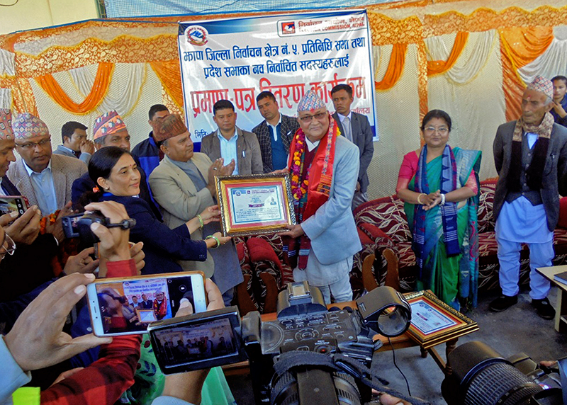 CPN-UML's Chairman and newly elected member of Federal Parliament from Jhapa 5 receives certificate from election officer Shakuntala Karki, in Bhadrapur, Jhapa district, on Monday, December 11, 2017. Photo: RSS