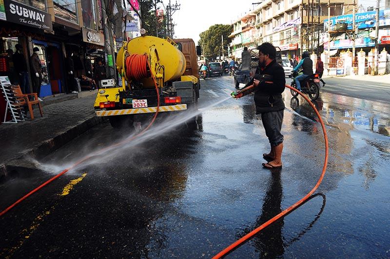 A staffer of Kathmandu Metropolitan City cleaning the road with water, in Kathmandu, on Friday, December 1, 2017. Photo: Balkrishna Thapa Chhetri