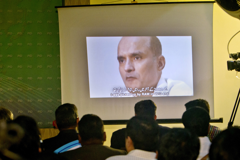 FILE - In this March 29, 2016, file photo, journalists look a image of Indian naval officer Kulbhushan Jadhav, who was arrested in March 2016, during a press conference by Pakistan's army spokesman and the Information Minister, in Islamabad, Pakistan. Pakistan's foreign ministry said on Sunday, December 24, 2017. Photo: AP