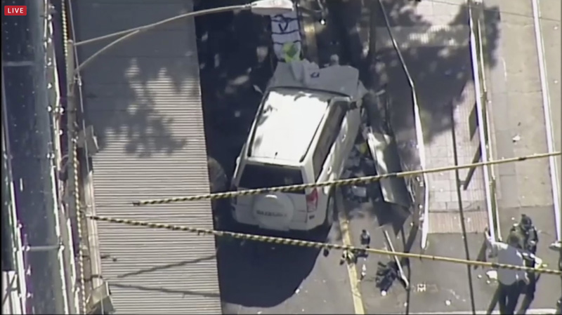 In this photo made video from the Australian Broadcasting Corp., a white SUV vehicle is stopped after allegedly striking pedestrians, Thursday, Dec. 21, 20217, in Melbourne, Australia. Local media say over a dozen people have been injured after a car drove into pedestrians on a sidewalk in central Melbourne. Photo: AP