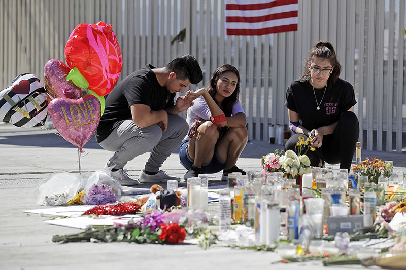 FILE - In this Oct. 3, 2017, file photo, Las Vegas residents, from left, Roberto Lopez, Briana Calderon and Cynthia Olvera, pause at a memorial site in Las Vegas two days after a man gunned down dozens of people from his high-rise hotel suite. Photo: AP