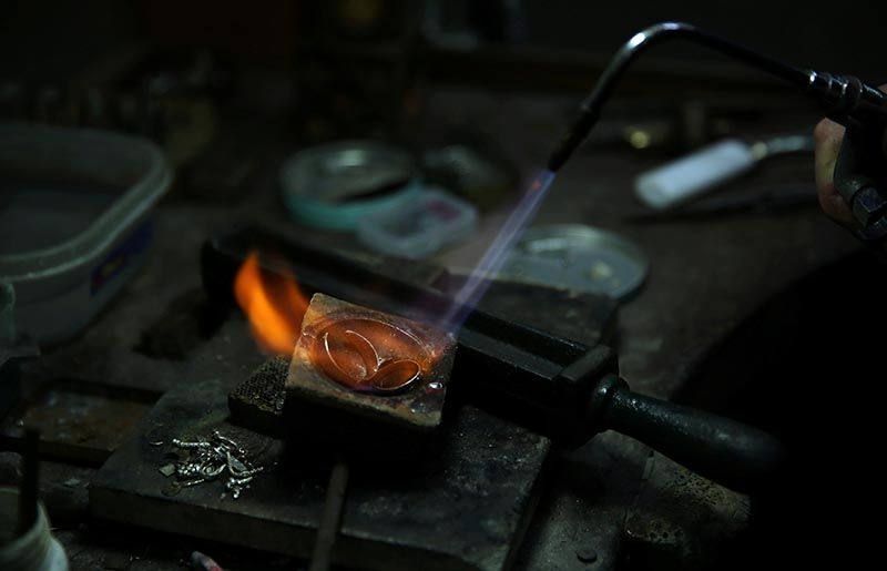 A goldsmith works on golden rings at his workshop in Buenos Aires, Argentina, on December 13, 2017. Photo: Reuters