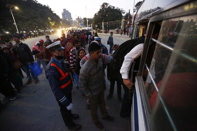 A traffic policeman making passengers stand in queue before boarding a bus in Ratnapark, Kathmandu, on Sunday, December 17, 2017. Photo: Skanda Gautam/THT