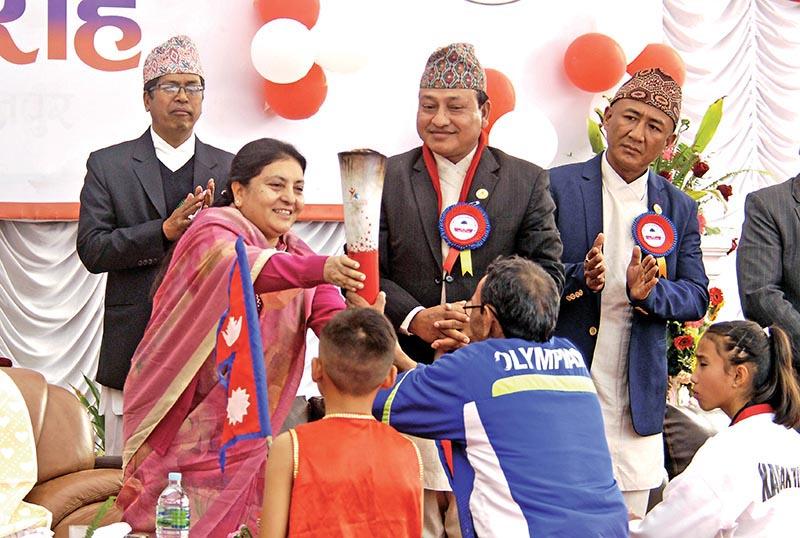 President Bidhya Devi Bhandari handing over Olympic Torch to first international medal winning legendary athlete Jeet Bahadur KC during the inauguration ceremony of the NSC Championship in Lalitpur on Sunday. Photo: Naresh Shrestha/ THT