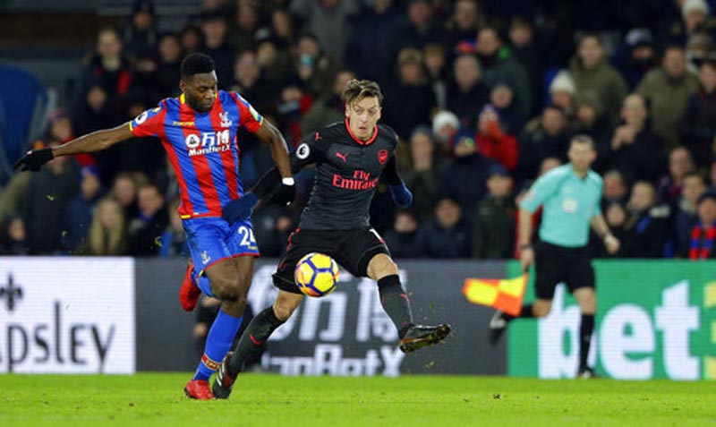 Arsenal's Mesut Ozil, right, vies for the ball with Crystal Palace's Timothy Fosu-Mensah during their English Premier League soccer match between Crystal Palace and Arsenal at Selhurst Park stadium in London, Thursday, Dec. 28, 2017. (AP Photo/Alastair Grant)