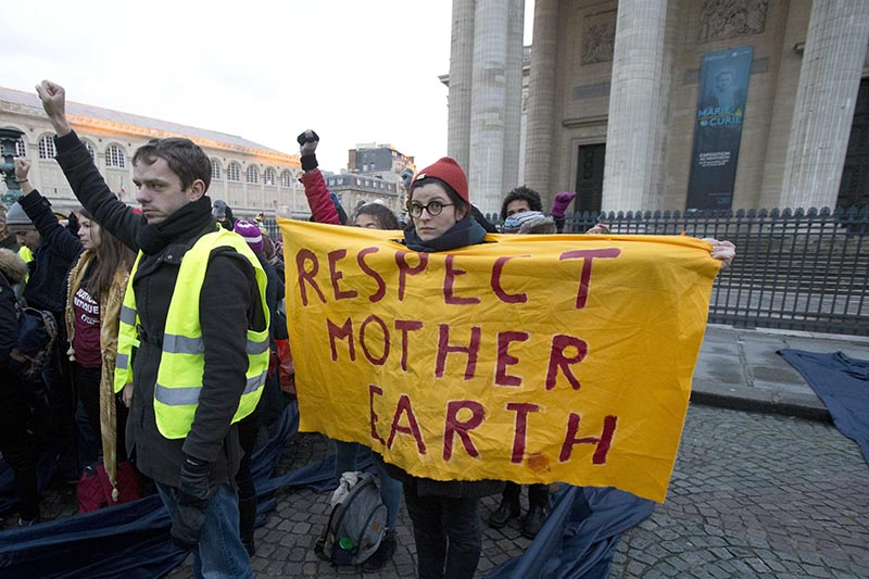An environmental activists displays a placard as she protests at Pantheon monument in support of the Paris climate accord, in Paris, France, on Tuesday, December 12, 2017. Photo: AP