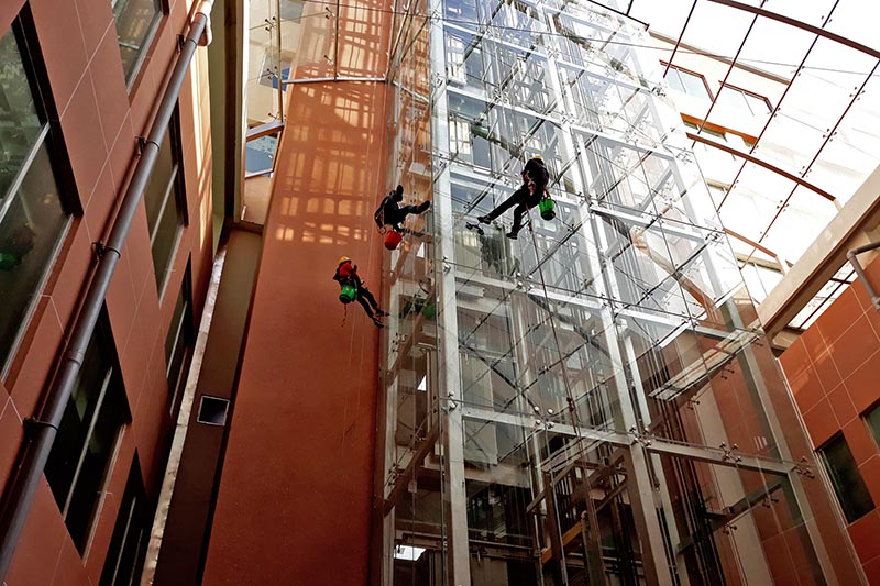Window cleaners are seen cleaning glass windows at Nepal Mediciti in Bhainsepati of Lalitpur district, on Sunday, December 3, 2017. Photo: RSS