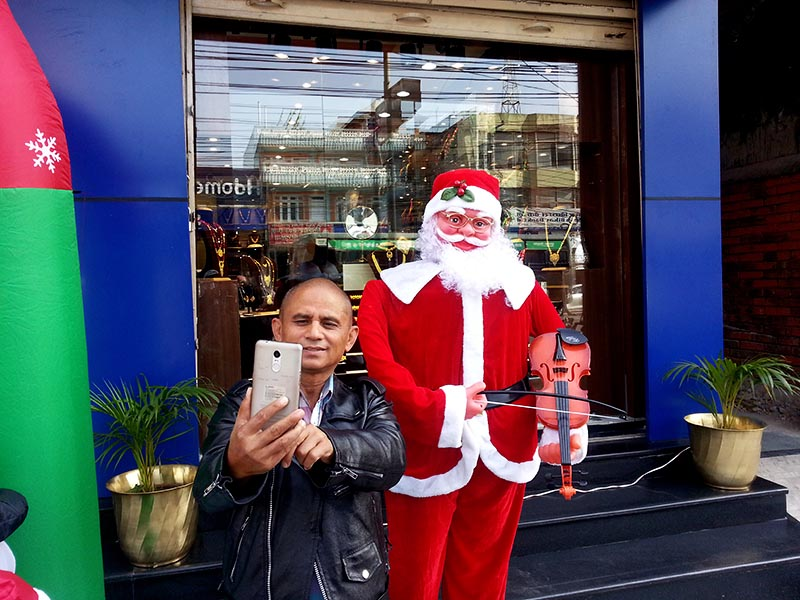 A person taking selfie with a mannequinn dressed as a Santa Clause  in New Road, Pokhara of Kaski district on Monday, December 25, 2017. Photo Rup Narayan Dhakal