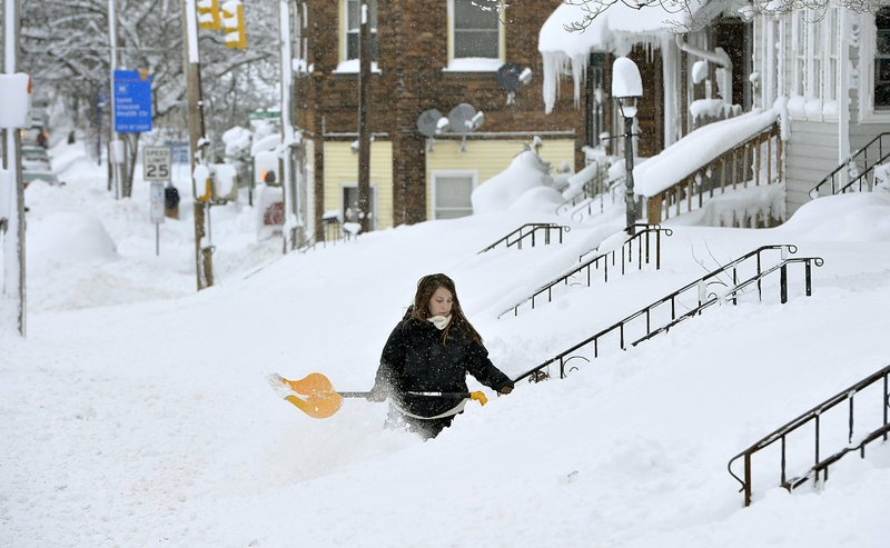 Rochelle Carlotti, 28, shovels steps near her home after a record snowfall on Tuesday, Dec. 26, 2017, in Erie, Pa. The National Weather Service office in Cleveland says Mondayu2019s storm brought 34 inches of snow, an all-time daily snowfall record for Erie. Photo: AP