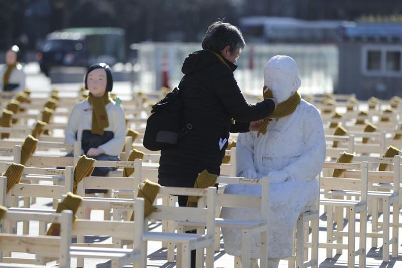 A woman puts a scarf on a statue of a comfort woman sitting in a installation of empty chairs symbolizing the victims in Seoul, South Korea, on Wednesday, December 27, 2017. Photo: AP