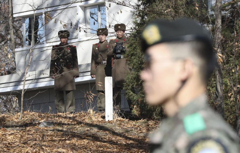 North Korean soldiers look at the South side as a South Korean stands guard near the spot where a North Korean soldier crossed the border at the Panmunjom, in the Demilitarized Zone, South Korea. South Korea says on Thursday, Dec. 21, 2017. Photo: AP