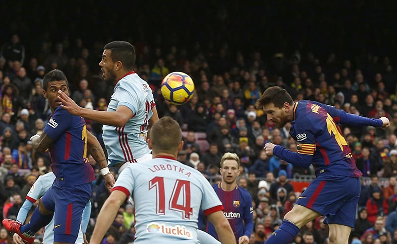 FC Barcelona's Lionel Messi (right), heads the ball during a Spanish La Liga soccer match between FC Barcelona and Celta Vigo at the Camp Nou stadium in Barcelona, on Saturday, December 2, 2017. Photo: AP