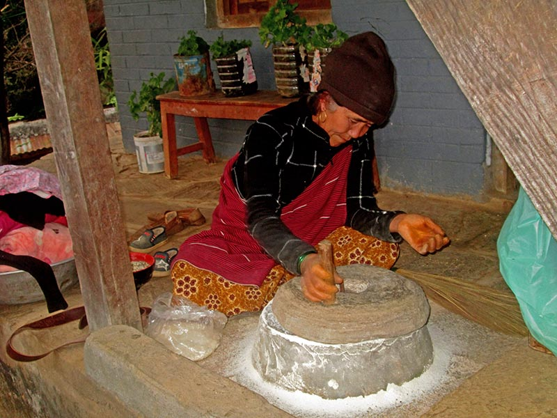 An elderly women grinding grains in tradition way in Ghale village of  Machhapuchhre Rural Municipality, Kaski district, on Tuesday, December 26, 2017. Photo: Rishi Ram Baral