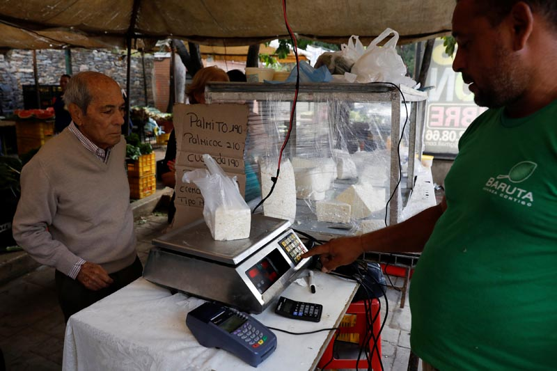A vendor weighs cheese for a customer at a street market in Caracas, Venezuela on December 19, 2017. Photo: Reuters