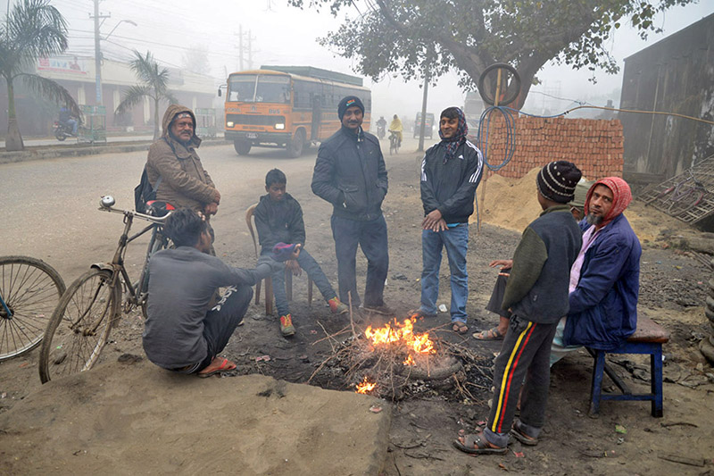 People gather around wood-fire to keep themselves warm in the cold-wave hit area in Birgunj, on Tuesday, December 19, 2017. Photo: RSS