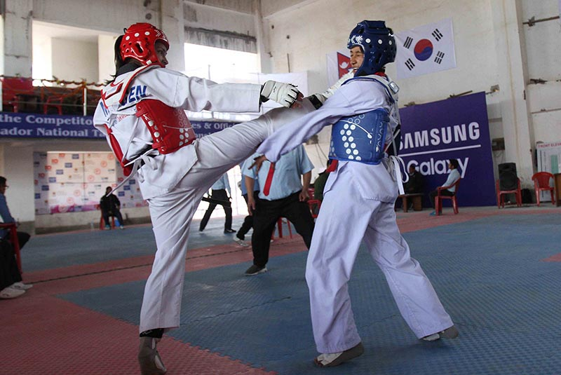 Dikchhya Karki (right) fights against Smita Shrestha during their below-53kg bout of the eighth Korean Ambassador Open Taekwondo Championship at the Nepal Taekwondo Academy hall in Lalitpur on Friday, December 15, 2017. Photo: Udipt Singh Chhetry/THT