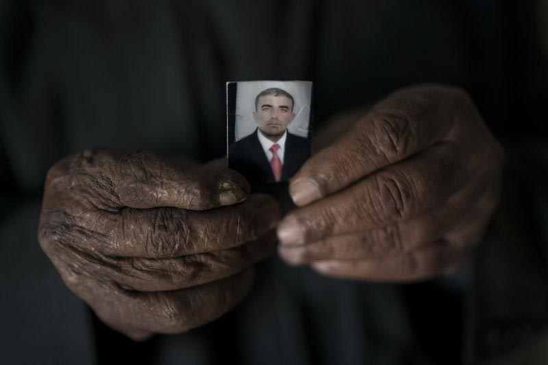 Ghanim Ahmed holds the photo of his son Ghazwan Ahmed, who was taken by unidentified gunmen after their village was liberated from Islamic State militants, in Bijwaniya village, south of Mosul, Iraq. Ghazwan was taken along with four other young men in August and despite months of searching; their families havenu2019t been able to locate them. (AP Photo/Felipe Dana)