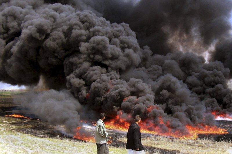 Iraqi men watch an oil pipeline fire burning in Hawija, near Kirkuk, Iraq. Iraq has invited bidders to express interest to build an oil pipeline that sends crude to international market through Turkeyu2019s Mediterranean port of Ceyhan.,on April 4, 2017. Photo:AP