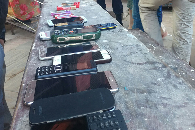 Mobile phones, lighter and cigarette packets are seen kept on a table. Security personnel has prohibited voters from taking those items along while casting votes, in Lalitpur-2, on Thursday, December 7, 2017. Photo: Rewati Sapkota