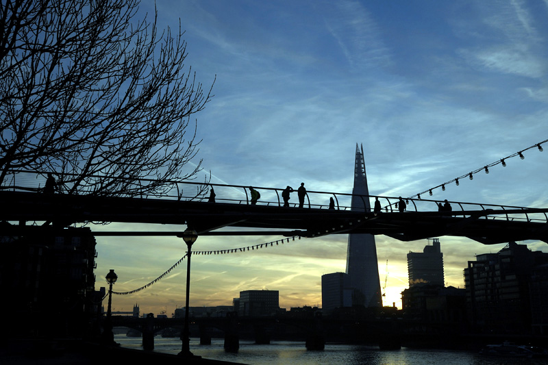 Workers cross the Millennium footbridge at dawn with the Shard skyscraper seen behind in London, Britain, December 19, 2017. Photo: Reuters