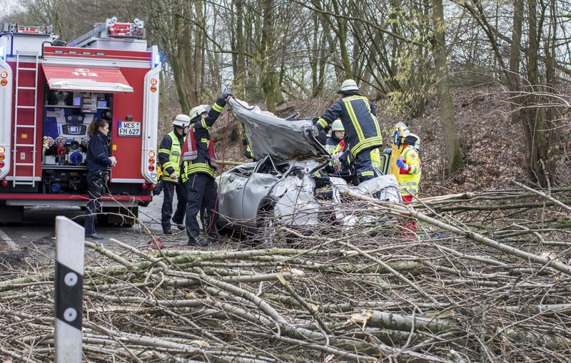 Rescue workers are busy at the site where a car was hit by a falling tree during a storm in Moers, western Germany, Thursday, Jan. 18, 2018. The driver was seriously injured in the accident. Photo: AP
