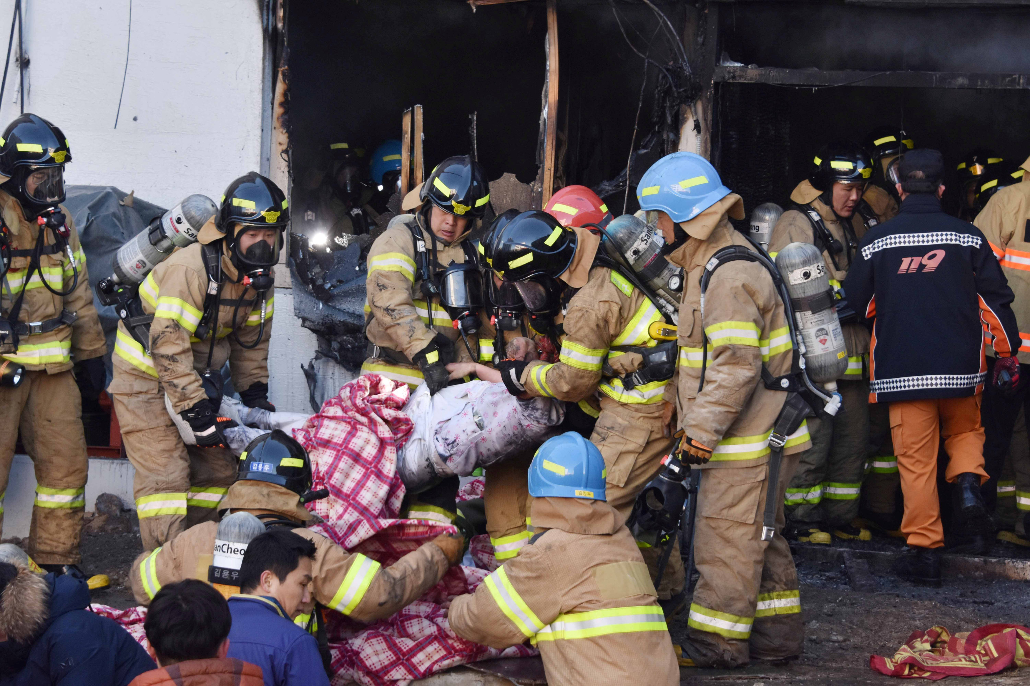 Firefighters rescue a patient from a burnt hospital in Miryang, South Korea, January 26, 2018.   Kim Gu-Yeon/Gyeongn Domin Ilbo/Handout via REUTERS ATTENTION EDITORS - THIS PICTURE WAS PROVIDED BY A THIRD PARTY. SOUTH KOREA OUT.