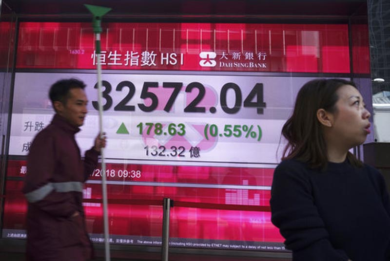 People walk past a bank electronic board showing the Hong Kong share index at Hong Kong Stock Exchange Tuesday, Jan. 23, 2018. Asian stock markets posted strong gains on Tuesday, as an upbeat forecast for global economic growth and the end of the U.S. government shutdown added to the market's optimistic mood. (AP Photo/Vincent Yu)