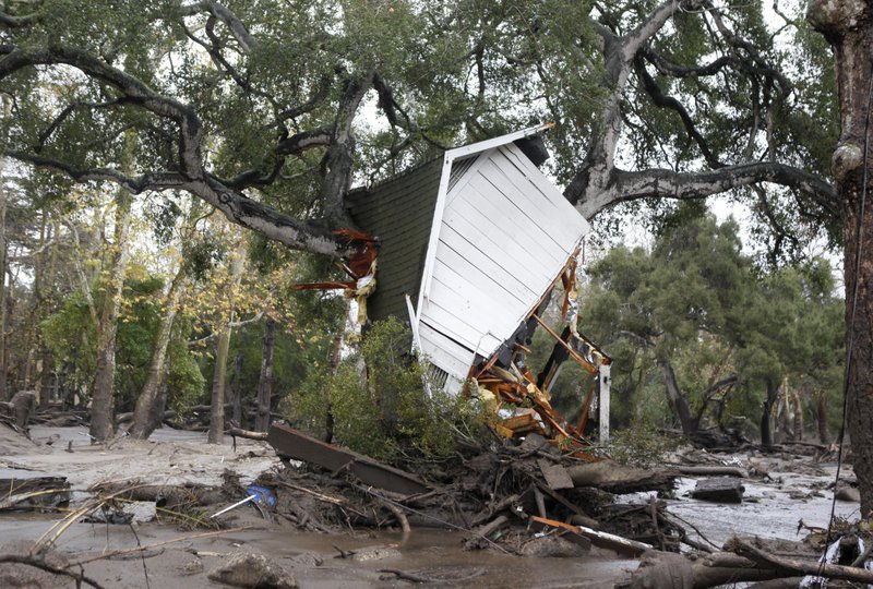 A structure is smashed against a tree along Hot Springs Road in Montecito, Calif. after getting hit by a flash flood and debris flow on Tuesday, Jan. 9, 2018. Several homes were swept away before dawn Tuesday when mud and debris roared into neighborhoods in Montecito from hillsides stripped of vegetation during a recent wildfire. (Daniel Dreifuss)