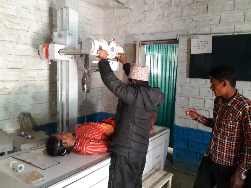 Office Assistant Dil Bista operating X-ray machine at District Public Health Office, in Bajura, on Friday, January 5, 2018. Photo: Prakash Singh/THT