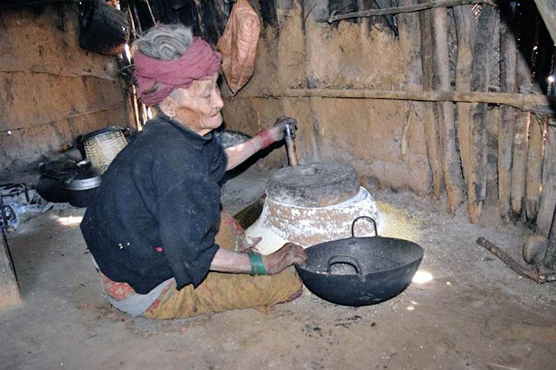 FILE - An elderly chepang woman grinding maize at a traditional stone grinder at  Brussbang village in Dhading district, on Sunday, January 07, 2018. Photo: Keshav Adhikari