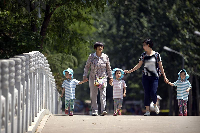 Women walk with children wearing matching hats as they cross a bridge at a public park on International Children's Day in Beijing, on June 1, 2017. Photo: AP