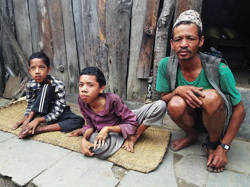 A man along with his two disabled sons sitting outside his house, in Gaurishankar Rural Municipality, Dolakha, on Saturday. Photo: THT